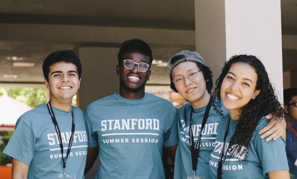 Four student staff members smile at the camera with their arms around each other.